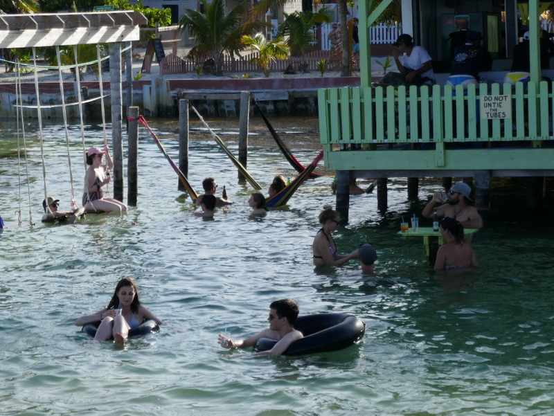 Tourists are drinking rum punch in a water bar in Caye Caulker, Belize.